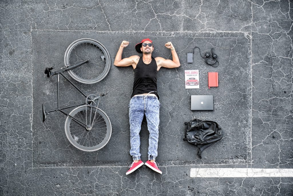 A guy in hat and sunglasses laying on asphalt with a bike, computer equipment staring into the sky and dreaming about being a business owner